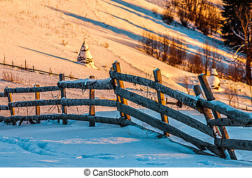 fence on snowy mountain slope near the forest in winter