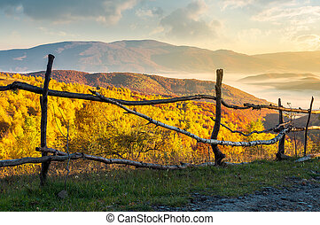 fence on the country road at sunrise. beautiful autumn...