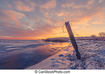Fence post by a frozen lake