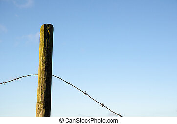 Fence post with old barb wire at blue sky