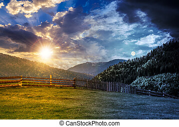 fence through the grassy meadow in mountains time change...