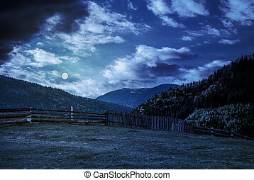fence through the grassy meadow in mountains at night in...