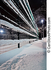 fence under the snow and street lamp in the winter park
