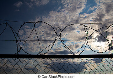 fence with barbed wire against the sky