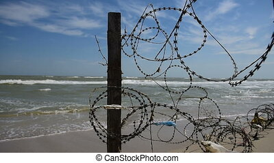 Fence with barbed wire on background of sea - Fence with...