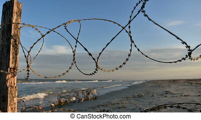 Fence with barbed wire on background of sea - Silhouettes of...