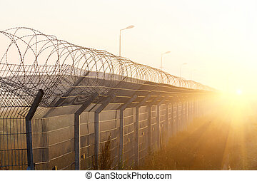 fence with barbed wire on the border