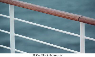 Fence with wooden handrail on deck of ship which floats in sea