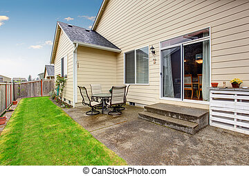Backyard area with patio table set. Beige house exterior.