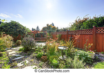 Fenced backyard with small garden and wooden hanging bench