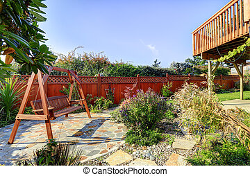 Fenced backyard with garden and hanging bench