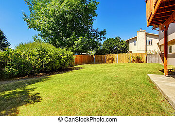Fenced backyard with green lawn and bushes.