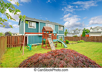 Small fenced backyard with playground for kids with chute, swings and climbing board