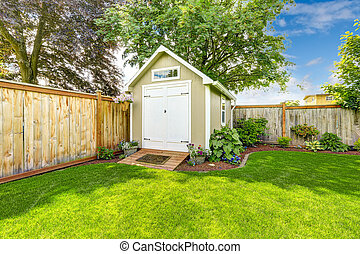 Fenced backyard with small shed