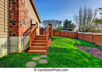 Fenced backyard with wooden walkout deck