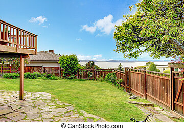 Fenced backyard with lawn and stoned tile floor. View of lake.