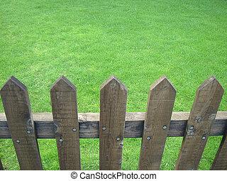 Wooden fenced fresh green lawn