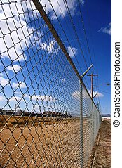 Fenced Out - Chain link fence topped with barbed wire...