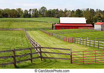 Fenced green pastures with a red barn in a rural landscape setting surround by trees.