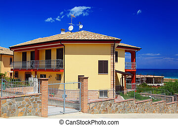 Fenced yellow two-story cottage with garden snd balcony on...