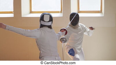 Fencer athletes during a fencing training in a gym - Front ...