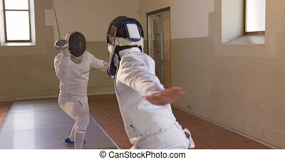 Front view of a Caucasian and a mixed race male fencer athletes during a fencing training in a gym, sparring in fencing duel wearing masks, taking aim at each other with their epees, one man succeeding in slow motion