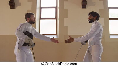 Fencer athletes during a fencing training in a gym
