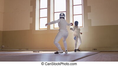 Fencer athletes during a fencing training in a gym - Low ...