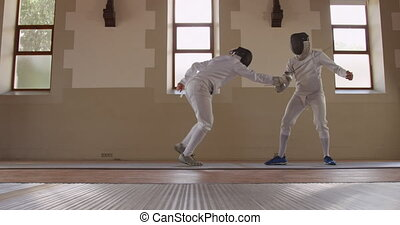Side view of a Caucasian and a mixed race male fencer athletes during a fencing training in a gym, sparring in fencing duel wearing masks, jumping taking aim at each other with their epees, one man succeeding and taking his mask off in slow motion