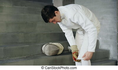 Fencer man putting on protective clothes and helmet prepare...