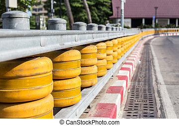 Fences on curve of the road in Thailand - Yellow fences on ...