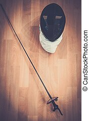 Fencing mask and epee on a floor