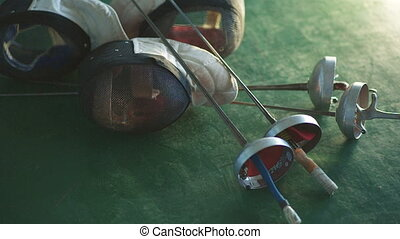 fencing mask and foil on the floor