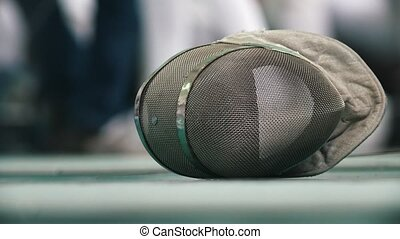 Fencing protective mask on the floor during sport...
