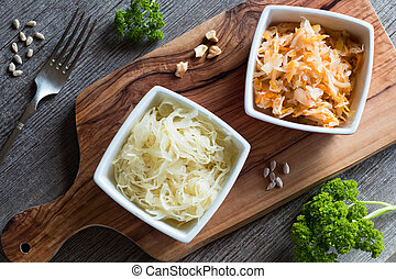 Fermented cabbage and carrots in two square bowls on a table...
