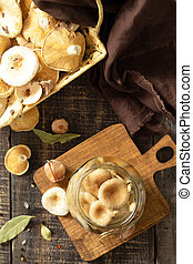 Fermented food: Mushroom preservation. Home preservation of products: glass jars with pickled mushrooms with spices on a rustic wooden table. Top view flat lay.