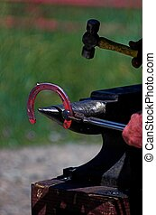 ferrier working glowing red horseshoe while practicing the art of hot shoeing a horse