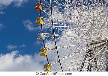 Ferris giant wheel against blue sky in funfair park