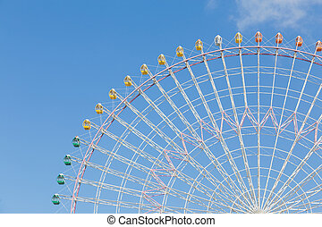 Ferris wheel against blue sky background
