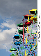 Ferris wheel against blue sky with clouds