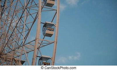 Ferris wheel against the blue sky in the amusement park.