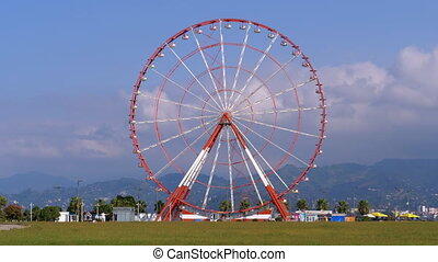 Ferris Wheel against the Blue Sky with Clouds near the Palm Trees in the Resort Town, Sunny Day