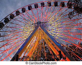 Ferris Wheel At Nigh - A colorfully lit up ferris wheel at...