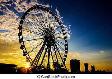 Ferris wheel in black silhouette at sunset.