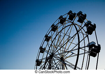 Ferris wheel in evening silhouetted against sky with copy space on the left