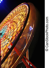 Ferris wheel in full spin - Motion blurred night shot of a...