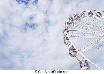 Ferris wheel in the cloudy blue sky
