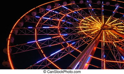 Ferris Wheel Lights at Night. Neon colored lights flashing...