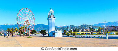 Ferris wheel, city panoramic banner landscape with palm teers and mountain peaks of Batumi, Georgia summer Black sea resort