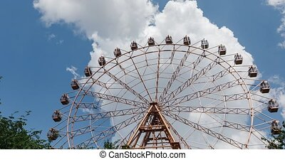Ferris wheel on blue sky with clouds background in fair park, timelapse video.